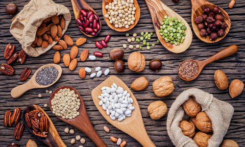 Selection of nuts, grains and pulses on a wooden board
