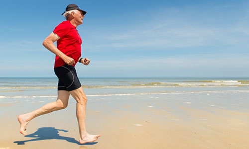 Senior man running on beach