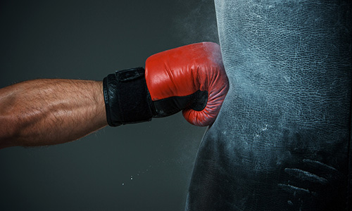 Boxing glove hitting punch bag
