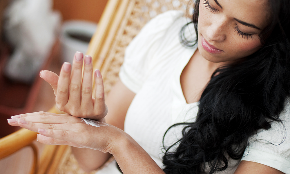 Image: woman applying hand cream. Click here for a Beginner's Guide To Relaxing