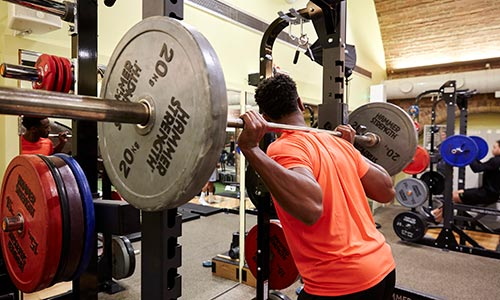 Gym Training - man lifting barbell with heavy weights