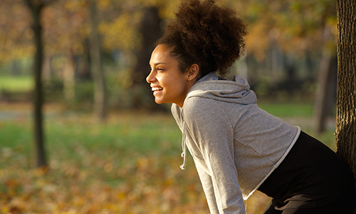 Smiling woman resting in the park after exercise