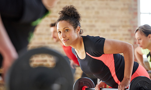 Gym class - woman with barbell doing body pump