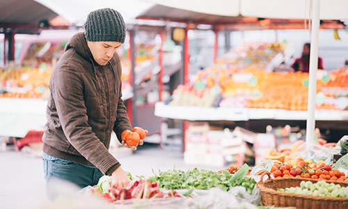 Man in winter clothes selecting tomatoes at a market