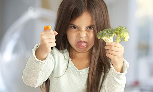 Fussy eating - girl turning her nose up at vegetables