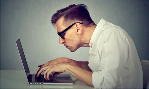 Man leaning uncomfortably over his laptop at a desk