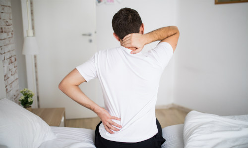 Back pain - man in bedroom holding back
