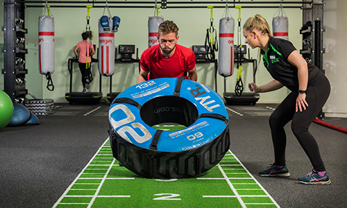 Functional training - man lifting tyre in gym with a female personal trainer assisting