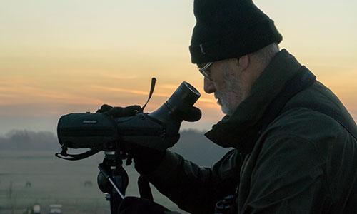 Man looking through a telescope at dawn