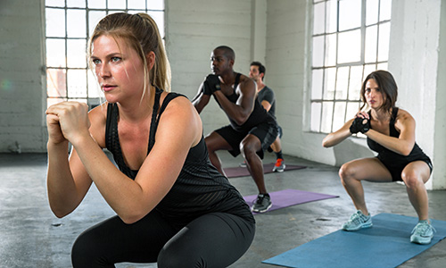 Woman leading an exercise class doing squats