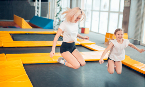 family fitness - Mum and daughter bouncing on trampoline