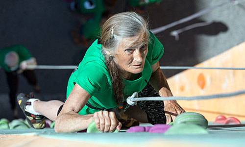 Active older woman rock climbing