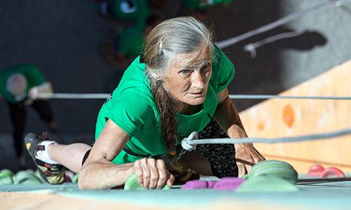 Active older woman rock climbing