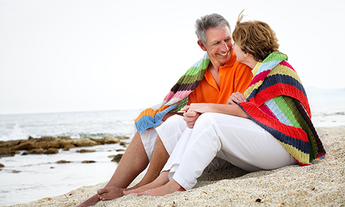 Happy couple in 50s wrapped in blanket on the beach