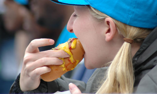 Woman eating a hotdog at sporting event