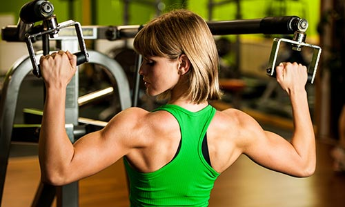 Gym training - woman with strong arm muscles performing a pull down