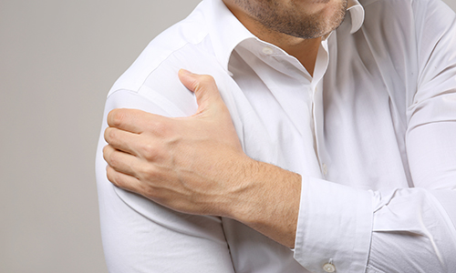 Man in white shirt clutches his shoulder in pain. close up