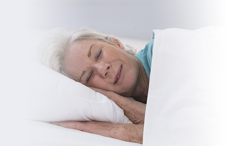 Older woman sleeping in white sheets in bed