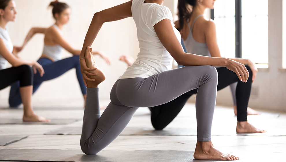 Women during exercise class doing leg stretches