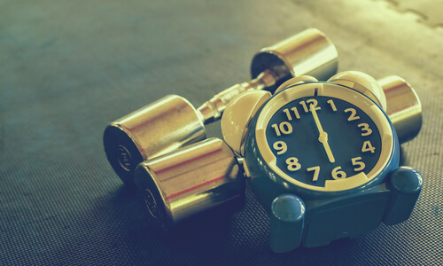 Clock and dumbells on a gym mat