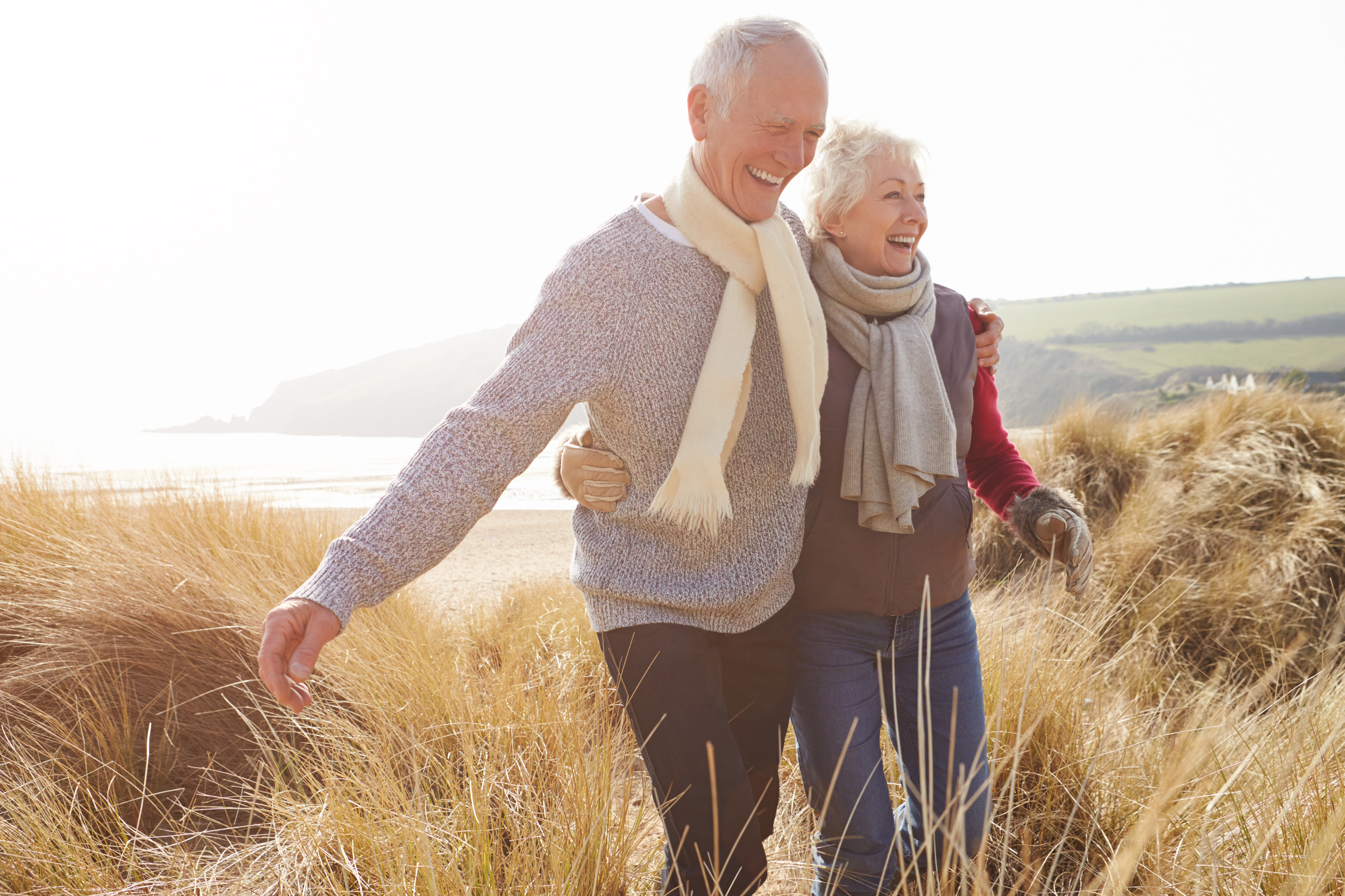 Hip pain - happy elderly couple roaming through fields