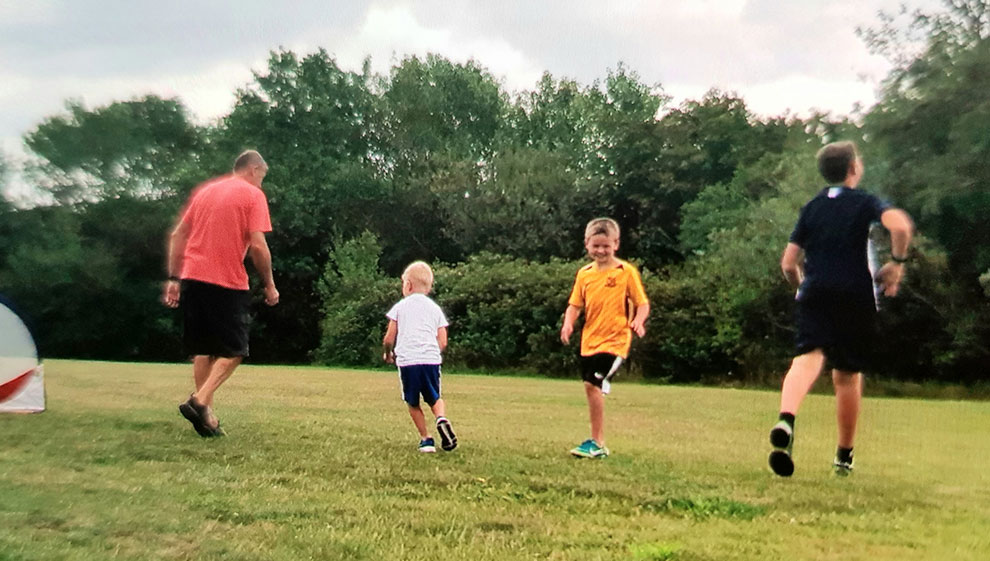 Bob McLintock playing football with his grandsons