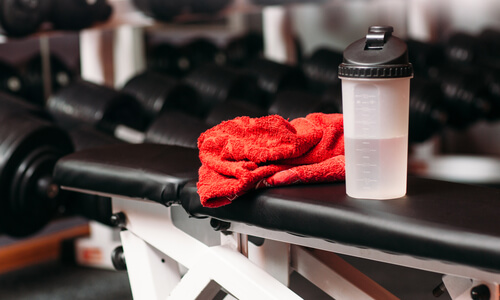 Sports water bottle and red towel on a weights bench