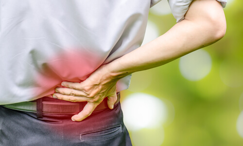Man clutching at his lower back in pain