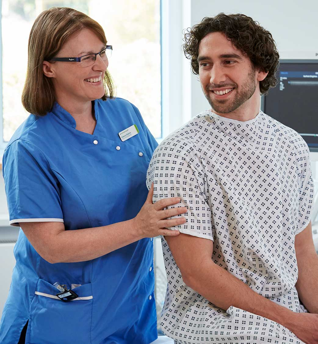 Nurse with man in hospital gown smiling