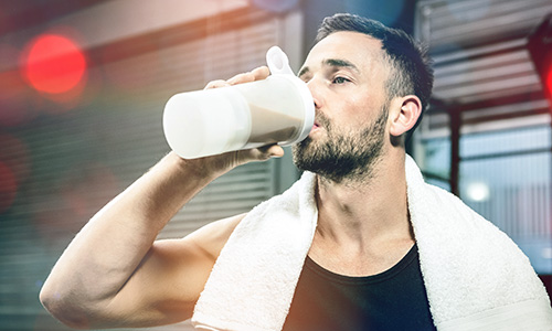 Fitness nutrition - man drinking protein shake full of macros