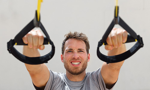 Pulley Workout - man pulling cables towards him with strained face