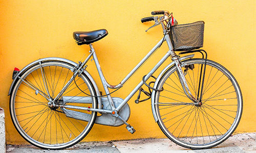 Bike with basket leaning on a yellow wall