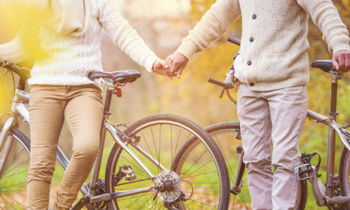 Older couple holding hands on cycle