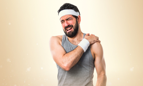 Man in sportswear holding his shoulder in animated pain