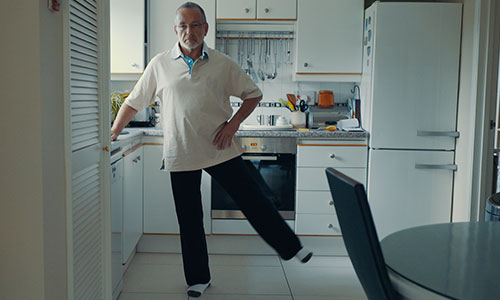 Man performing side leg raises while standing in kitchen