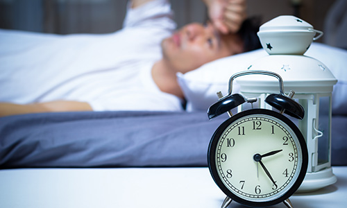 Man struggling to get to sleep