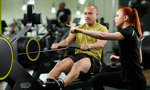 Man being shown how to use rowing machine by Personal Trainer