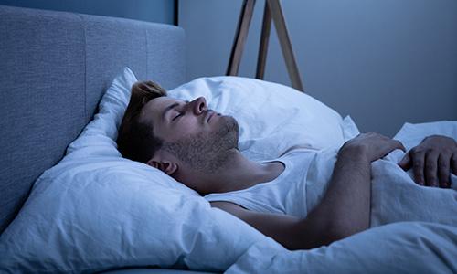 Man lying in bed, sleep paralysis